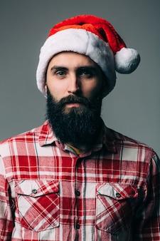 灰色の壁に赤いクリスマスの帽子を持つ若いハンサムなひげを生やした男