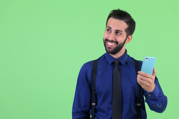 Молодой красивый бородатый персидский бизнесмен у зеленой стены