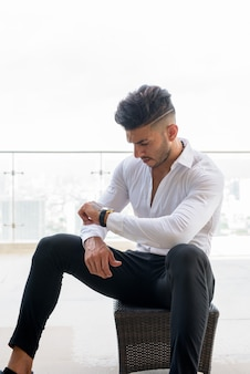 Young handsome bearded persian businessman checking the time against view the city