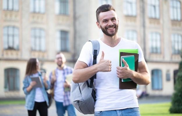 バックパックと本を手にカジュアルな服を着た若いハンサムなひげを生やした学生の男は、大学の建物の上を歩いてポーズをとっています