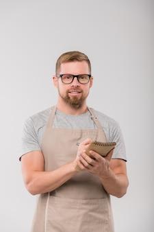 Молодой красивый бородатый официант в фартуке и очках записывает заказ клиента перед камерой изолированно