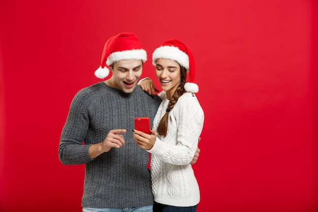 Young handsome and beautiful couple enjoy checking on mobile phone in christmas day.