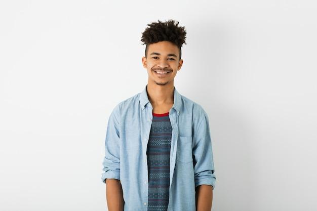 Giovane uomo di colore bello, espressione del viso sorridente, guardando a porte chiuse, stato d'animo positivo, emozione felice, isolato su sfondo bianco studio, gioventù afroamericana, stile hipster, studente, camicia blu