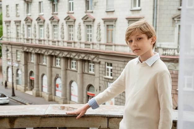 발코니에 포즈 베이지 색 스웨터에 젊은 잘 생긴 금발 남자