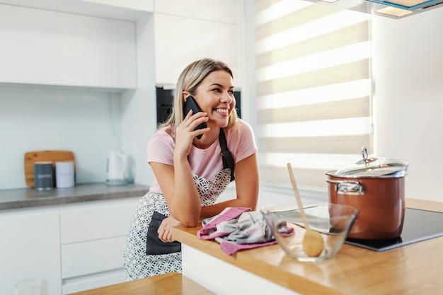 Молодая красивая блондинка ленивая домохозяйка стоит на кухне, разговаривает по телефону, пока горшок с обедом стоит на плите.