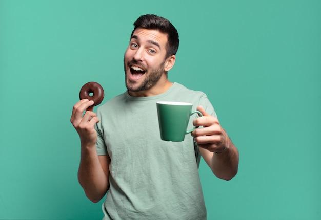 チョコレートドーナツとコーヒーカップを持つ若いハンサムな金髪の男。朝食のコンセプト