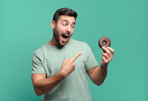 초콜릿 도넛과 젊은 잘 생긴 금발 남자. 아침 개념