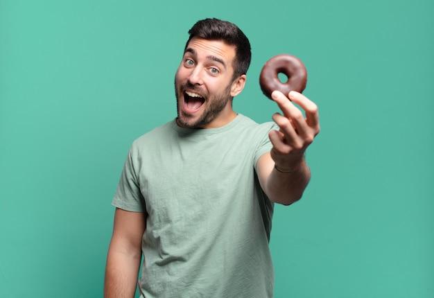 チョコレートドーナツを持つ若いハンサムなブロンドの男。朝食のコンセプト