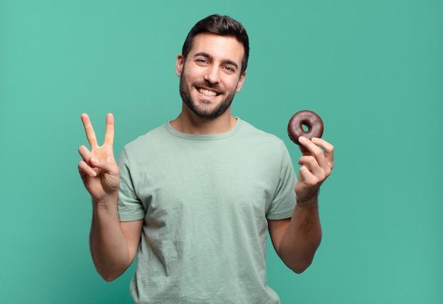 초콜릿 도넛과 젊은 잘 생긴 금발 남자
