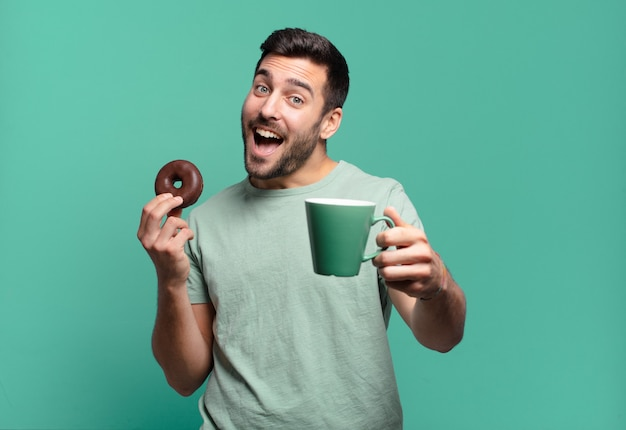 Young handsome blond man with a chocolate donut and a coffee cup. breakfast concept