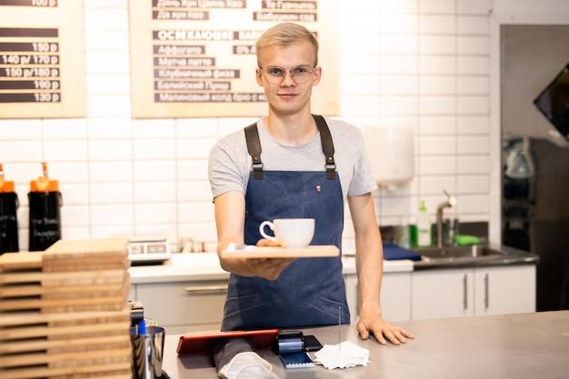 Молодой красивый белокурый официант в очках и спецодежде дает вам поднос с чашкой кофе, стоя у стойки