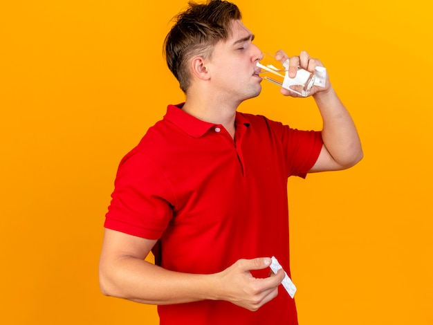 Young handsome blonde ill man holding napkin taking pill drinking water from glass isolated on orange wall