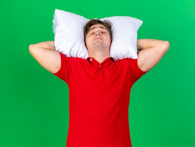 Il giovane uomo malato biondo bello che tiene il cuscino sotto la testa fa finta di dormire isolato su priorità bassa verde
