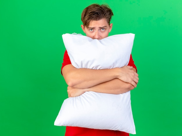 コピースペースで緑の背景に分離された後ろからカメラを見て枕を保持している若いハンサムな金髪の病気の男