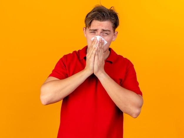 Молодой красивый блондин больной мужчина смотрит в камеру, вытирая нос салфеткой, изолированной на оранжевом фоне с копией пространства