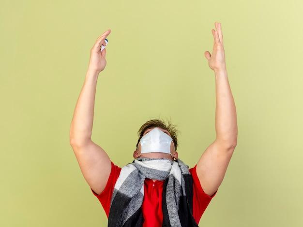 Молодой красивый белокурый больной мужчина в маске и шарфе держит термометр, глядя вверх, поднимая руки, благодарив бога, изолированного на оливково-зеленом фоне с копией пространства