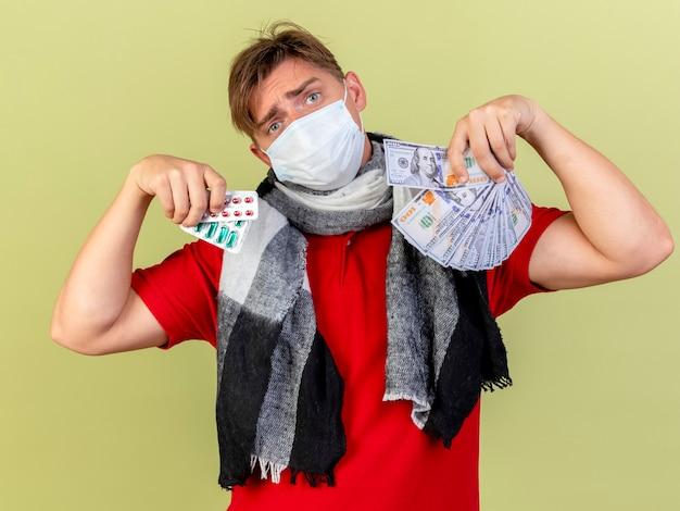 オリーブグリーンの背景で隔離のカメラを見てお金と医療薬のパックを保持しているマスクを身に着けている若いハンサムな金髪の病気の男