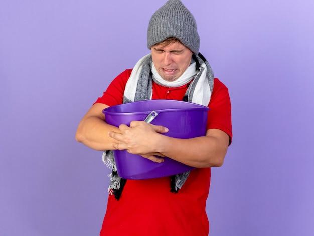 冬の帽子とスカーフを身に着けている若いハンサムな金髪の病気の男は、コピースペースで紫色の背景に分離された目を閉じて吐き気を持っているプラスチック製のバケツを保持しています