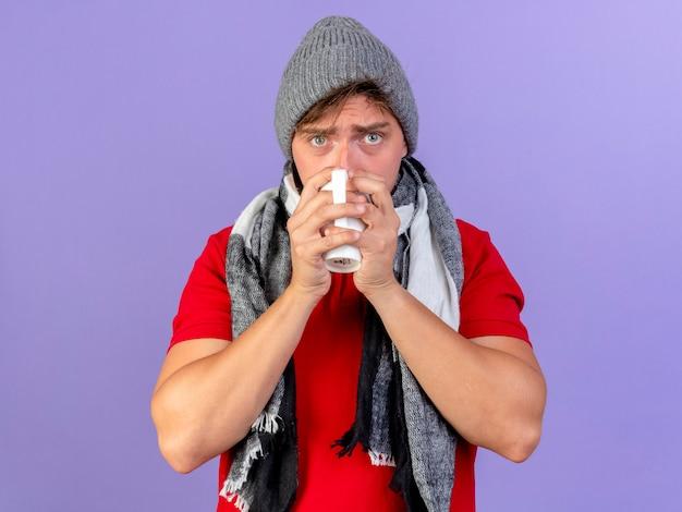 冬の帽子とスカーフを身に着けている若いハンサムな金髪の病気の男が紫色の背景で隔離のお茶を飲むカメラを見て
