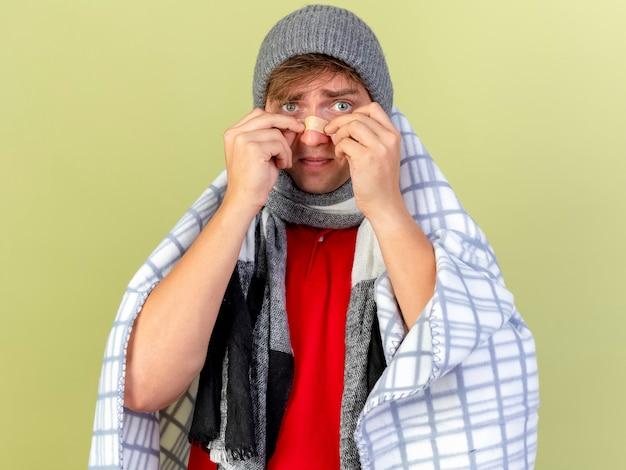 オリーブグリーンの壁に分離された鼻に石膏を置く格子縞に包まれた冬の帽子とスカーフを身に着けている若いハンサムな金髪の病気の男
