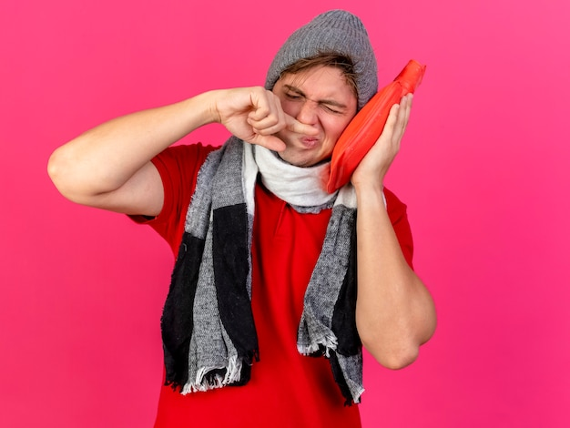 Giovane bella bionda uomo malato che indossa cappello invernale e sciarpa toccando il viso con la bottiglia di acqua calda pulendosi il naso con il dito con gli occhi chiusi isolato su sfondo cremisi con lo spazio della copia