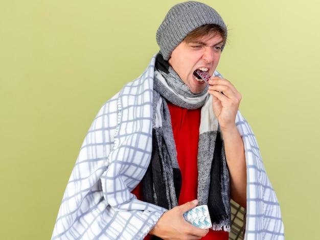 Giovane uomo malato biondo bello che indossa cappello invernale e sciarpa avvolti in un plaid che tiene confezioni di pillole mediche e mettendolo in bocca guardando dritto isolato sul muro verde oliva