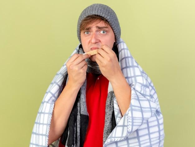 Giovane bella bionda uomo malato che indossa un cappello invernale e sciarpa avvolto in un plaid guardando la telecamera tenendo intonaco toccando il mento con esso isolato su sfondo verde oliva