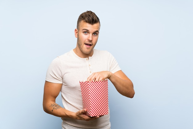 Young handsome blonde man over blue wall eating popcorns