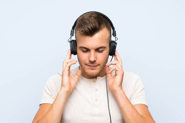 Young handsome blonde man over blue wall listening to music with headphones