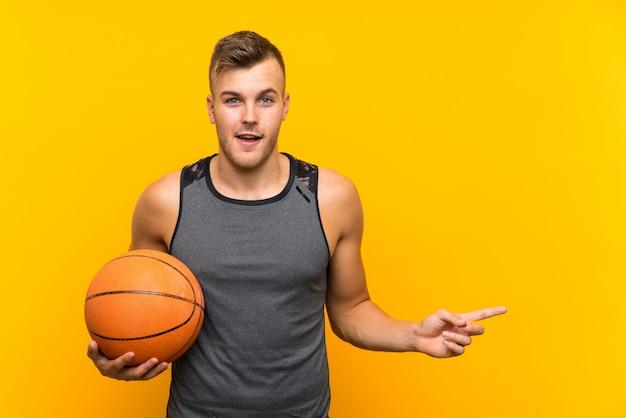 Молодой красивый белокурый человек, держащий баскетбольный мяч над изолированной желтой стеной удивлен и указывая пальцем в сторону