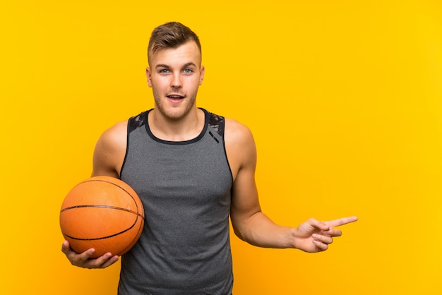 Young handsome blonde man holding a basket ball over isolated yellow wall surprised and pointing finger to the side