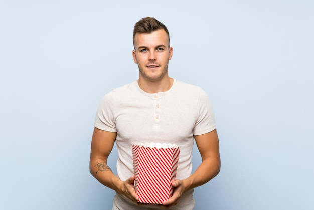 Young handsome blonde man holding a bowl of popcorns