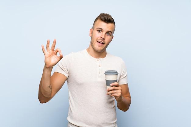 熱い一杯のコーヒーを保持している若いハンサムな金髪男