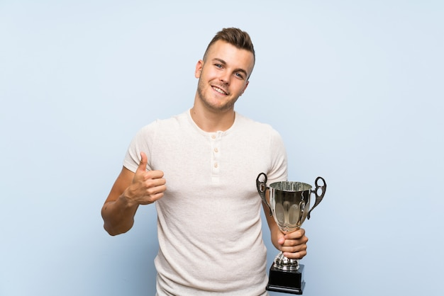 Young handsome blonde man holding a trophy