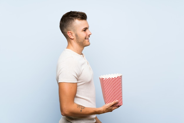 Young handsome blonde man over isolated blue background holding a bowl of popcorns