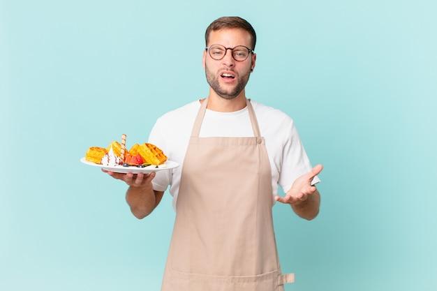 怒って、イライラして欲求不満に見える若いハンサムなブロンドの男。料理ワッフルのコンセプト