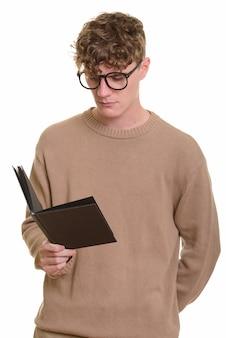 本を読んで眼鏡を持つ若いハンサムなブロンドの男