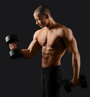 Молодой красивый культурист, демонстрируя его сексуальный разорвал тело работает с весами