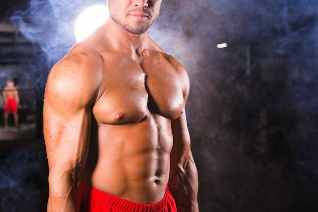 Young handsome bodybuilder sportsman in gym, close up