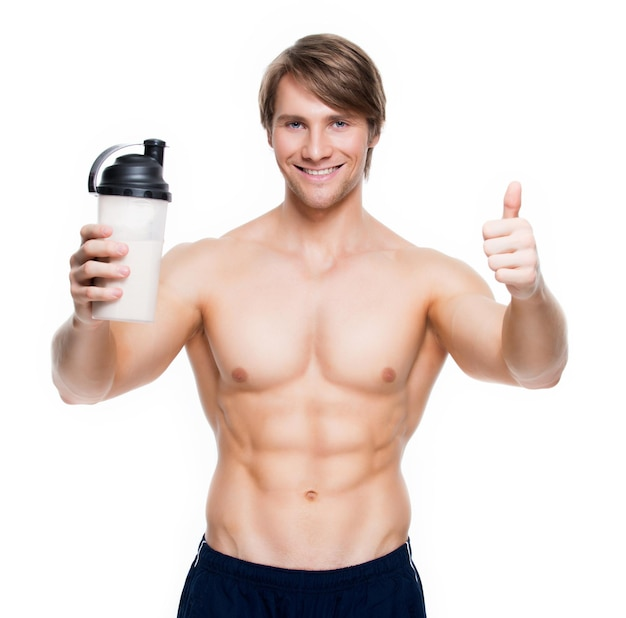 Young handsome bodybuilder with a bottle posing  on a white wall.