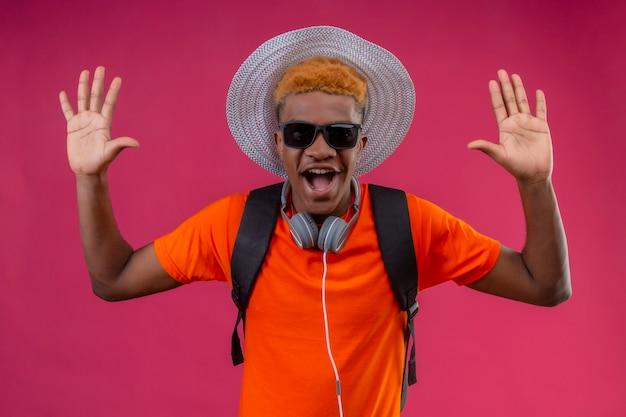 ピンクの壁を越えて降伏立って驚いて幸せな調達の手を探しているカメラで夏の帽子の若いハンサムな男の子