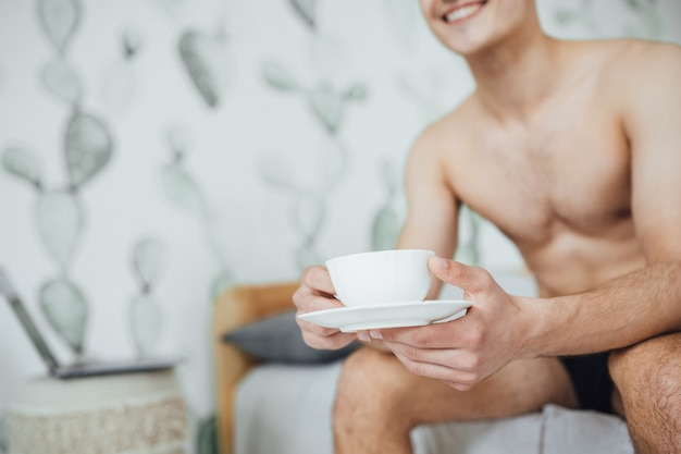 The young handsome boy is sitting in bed in his room and drinking coffee in the morning