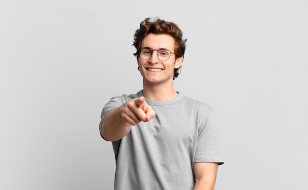 당신을 선택하는 만족스럽고 자신감 있고 친절한 미소로 앞을 가리키는 젊고 잘 생긴 소년