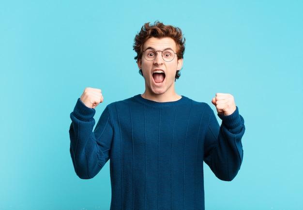 Молодой красивый мальчик агрессивно кричит с сердитым выражением лица или со сжатыми кулаками, празднуя успех