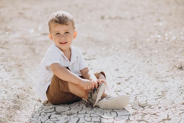 地面に座っている若いハンサムな男の子