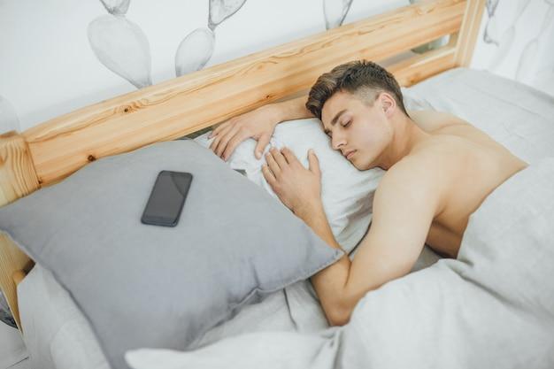 朝ベッドで寝ているハンサムな少年