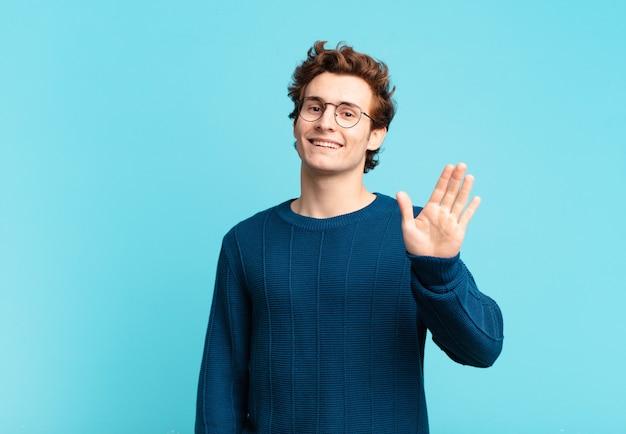 幸せで元気に笑って、手を振って、あなたを歓迎して挨拶するか、さようならを言う若いハンサムな男の子