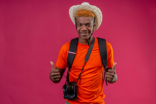 Young handsome boy in summer hat with camera happy and positive showing thumbs up with both hands standing over pink wall