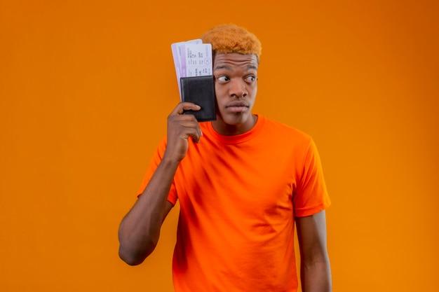 Молодой красивый мальчик в оранжевой футболке, держащий авиабилет, взволнованно смотрит в сторону, стоя у оранжевой стены