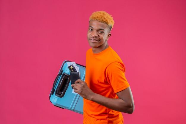 Молодой красивый мальчик в оранжевой футболке с дорожным чемоданом и билетами на самолет выглядит уверенно, улыбаясь позитивно и счастливо, стоя над розовой стеной